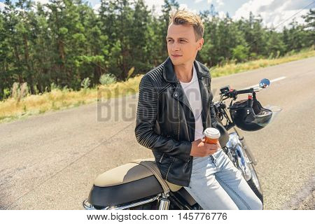 Invigorating coffee is what he needs. Handsome young guy sitting by motorcycle, parking along road and holding coffee