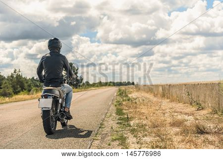 Only forward. Rear view of biker in black helmet riding by his motorcycle on road along field