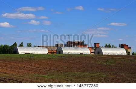Facilities of agribusiness against plowed field in spring