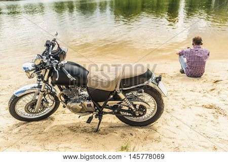 Music is always with me. Vintage motorcycle with helmet on handlebars parking on lake with guy listening to music in background