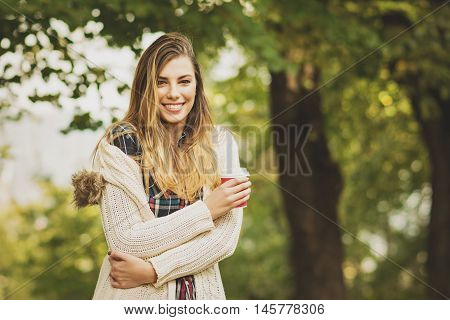Portrait of beautiful young blonde Caucasian woman, smiling, holding takeaway coffee cup, standing in park in autumn, wearing modern knitted beige sweater