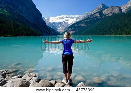 Woman standing on beach by Lake Louise in Rocky Mountains. Banff National Park. Alberta. Canada.