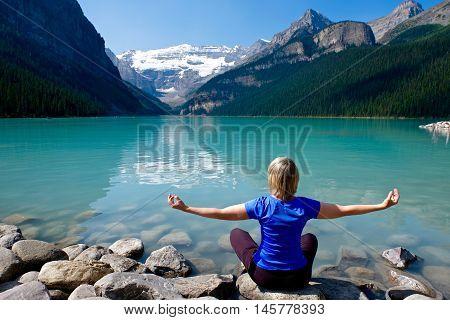 Woman at alpine lake meditating. Lake Louise in Rocky Mountains. Banff National Park. Alberta. Canada.