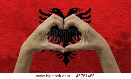 With a stylized Albanian flag background an anonymous person's hands being held in the form of a heart, symbolizing love and patriotism for Albania.
