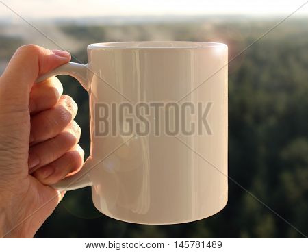 White mug in hand Mockup. Misty autumn forest on the background.