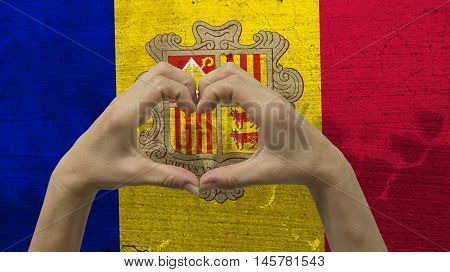 With a stylized Andorran flag background an anonymous person's hands being held in the form of a heart, symbolizing love and patriotism for Andorra.