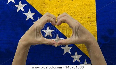 With a stylized Bosnian flag background an anonymous person's hands being held in the form of a heart, symbolizing love and patriotism for Bosnia and Herzegovina.