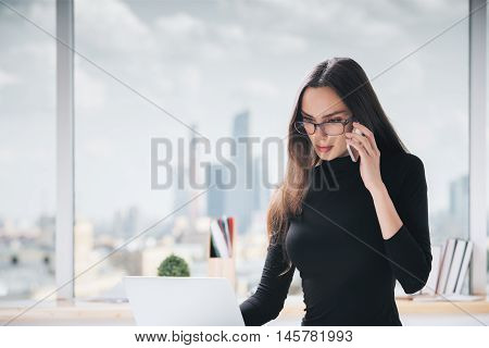 Woman On Phone Using Laptop