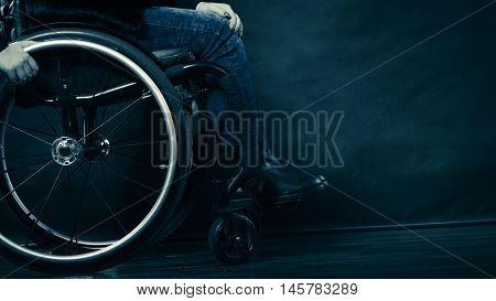 Real people disability and handicap concept. Young woman invalid girl sitting on wheelchair part of body studio shot on black poster