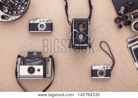 Many vintage cameras on wooden table. Photographer Desk. Photographer workplace. Tradional Photography. Black and White Photography. Negatives. Roll of films.