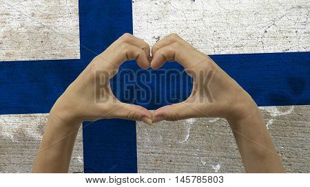 With a stylized Finnish flag background an anonymous person's hands being held in the form of a heart symbolizing love and patriotism for Finland.