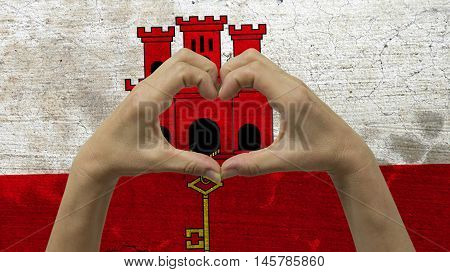 With a stylized Gibraltarian flag background an anonymous person's hands being held in the form of a heart symbolizing love and patriotism for Gibraltar.