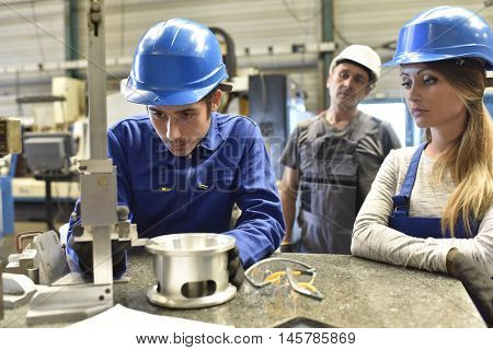 Young people in metallurgy training with instructor