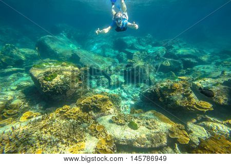 Female apnea swims in tropical turquoise sea of Racha Noi, Phuket in Thailand.