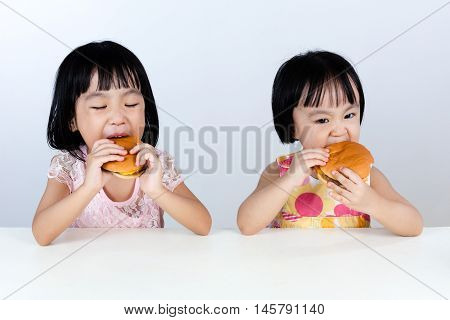 Two Asian Chinese Little Girl Eating Burger