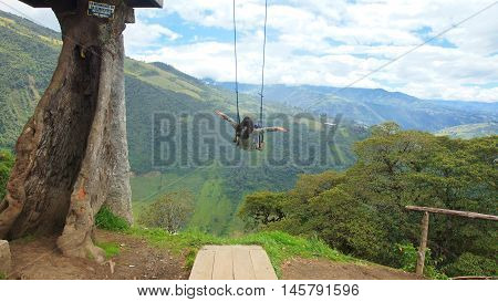 Young woman playing on the swing of the treehouse near of the city of Banos. Banos is located on the northern foothills of the Tungurahua volcano