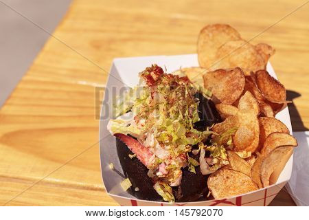 Gourmet Maine Lobster roll on a pumpernickel bun and potato chips at the beach in summer.