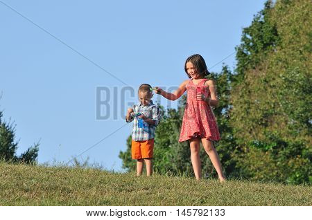 Happy litte brother and sister blowing bubbles out in a park