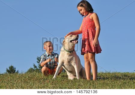 Happy brother and sister playing outside with their labrador dog