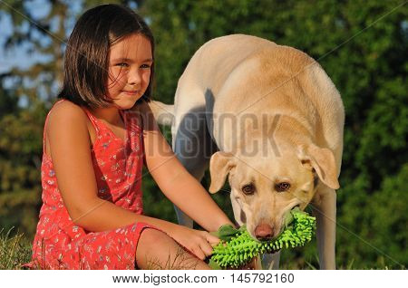 Happy little girl playing with her dog and toy outside