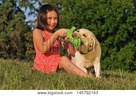 Cute girl playing with dog pulling on toy outside
