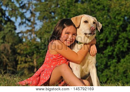 Happy child hugging her dog outside in the park