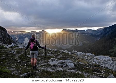 Woman watching sunset in mountains. Lake Ann trail in Cascade Mountain. Mount Baker National Forest. Washington. USA.