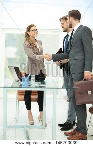 Business partners shaking hands in the modern office