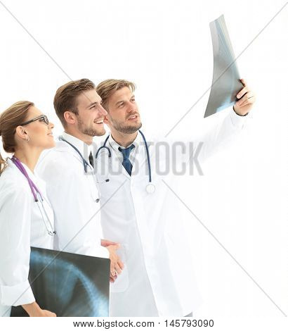 Three doctors looking attentively at x-ray and discussing it