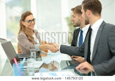 Happy business partners shaking hands in an office