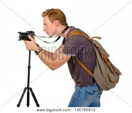 Young man traveler taking pictures by dslr camera on tripod isolated on white