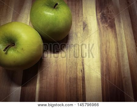green apples on a wooden cutting board