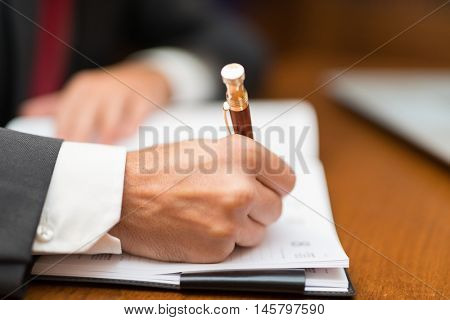 Businessman writing on his agenda