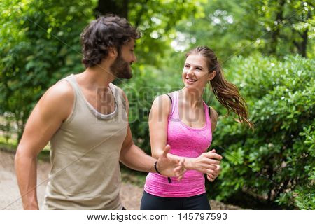 Smiling happy couple running in a park