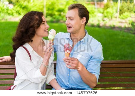 Portrait of an happy couple eating an ice cream in a park