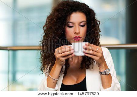 Portrait of happy brunette drinking coffee