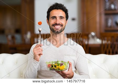 Man eating a salad in his living room
