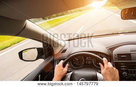 Detail of a man driving his car in the sunset