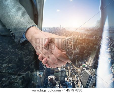 Double exposure of a business people shaking their hands in front of a big city
