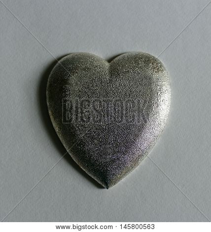 Silver textured heart isolated with copy space.