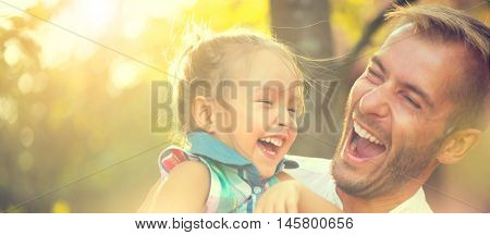 Happy joyful young father with his little daughter. Father and little kid having fun outdoors in orchard garden, playing together in summer park. Dad with his child laughing and enjoying nature