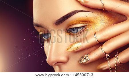 Beauty Fashion woman with Golden Makeup, gold accessories and nails. Model Girl Eyes with sparkling eyeshadows. Gold rings and manicure with crystals closeup on dark background. Fashion art make up