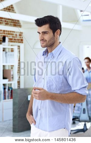Casual young man standing at office, looking away, side view.