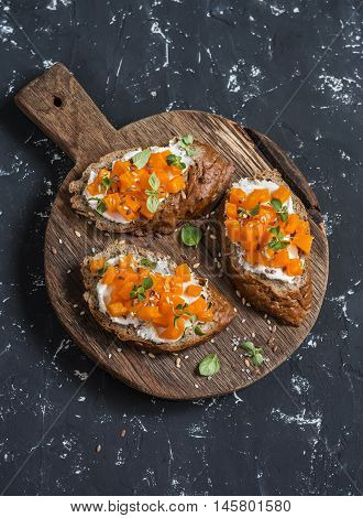 Pumpkin and goat's cheese bruschetta on a wooden cutting board on dark background. Healthy vegetarian snack