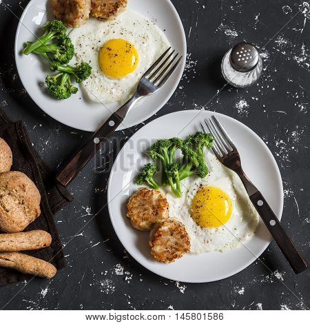 Fried eggs broccoli chicken meatballs homemade whole wheat bread - tasty simple dinner. On a dark background top view