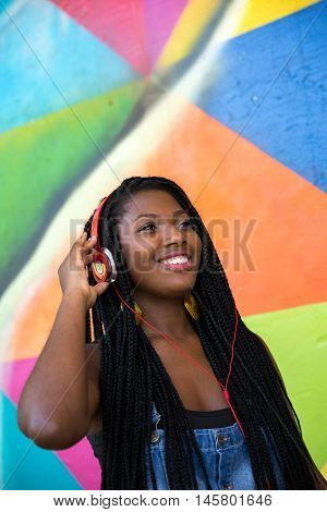 Happy african american young woman listening to music