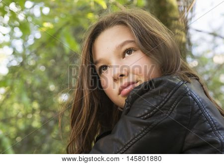 Happy and romantic teenager girl in a black jacket on a green foliage background