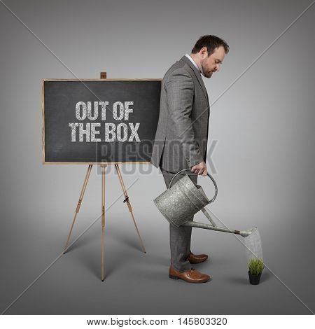 Out of the box text on  blackboard with businessman watering plant