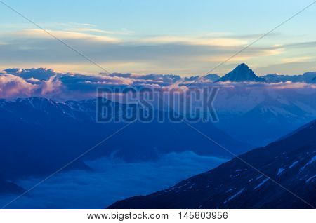 Mountains view at the top of the alps above the clouds