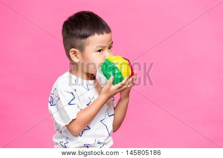 Young kid blowing with paper ball